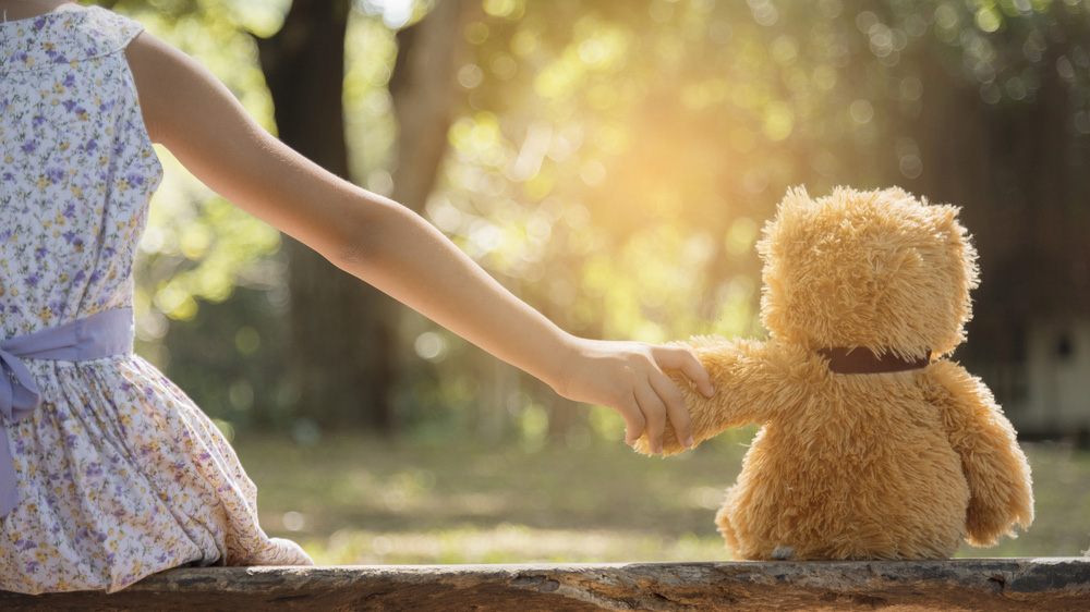 A young child holds a teddy bear.