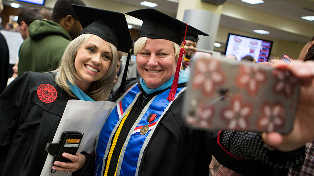 Two Cal U graduate students pose for a picture during Commencement.