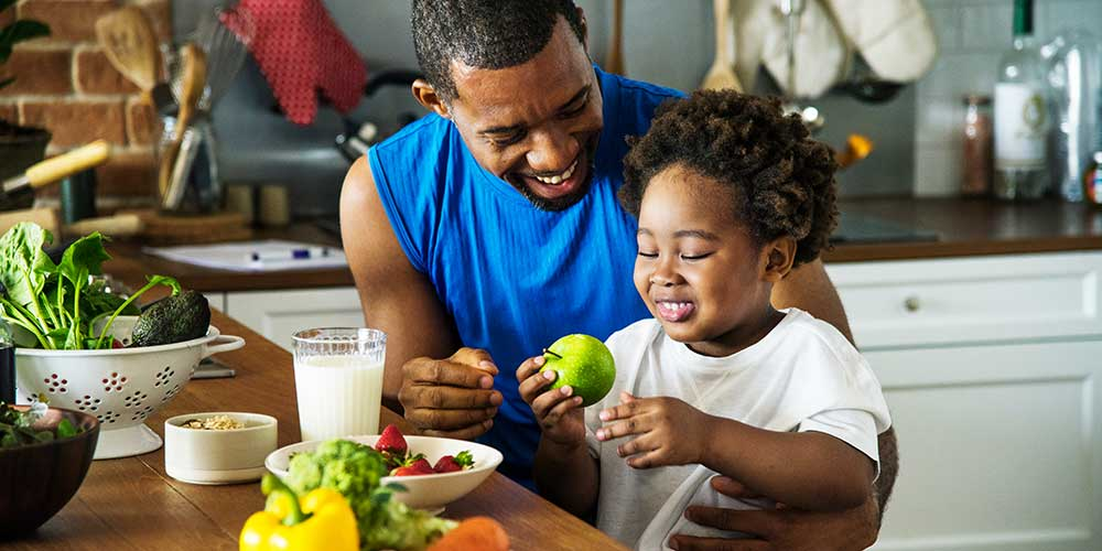 An online nutrition degree student at Cal U cooks with son.
