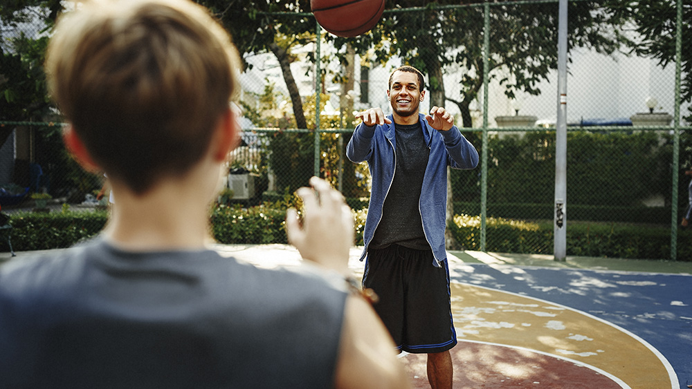 A man plays basketball with son.