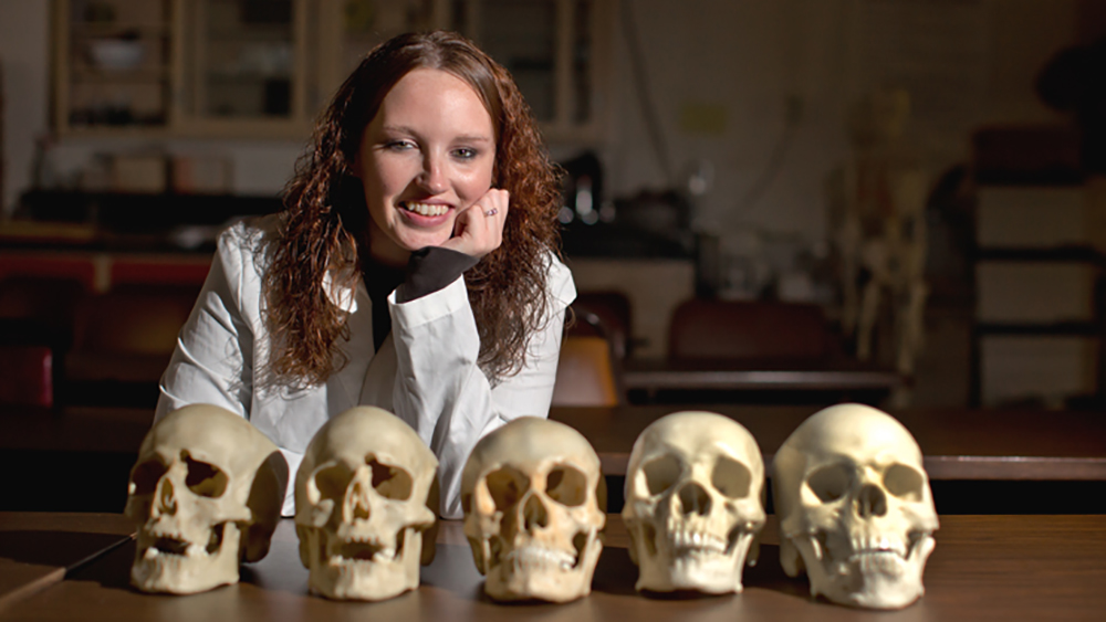 An archaeology student at Cal U poses with bones.