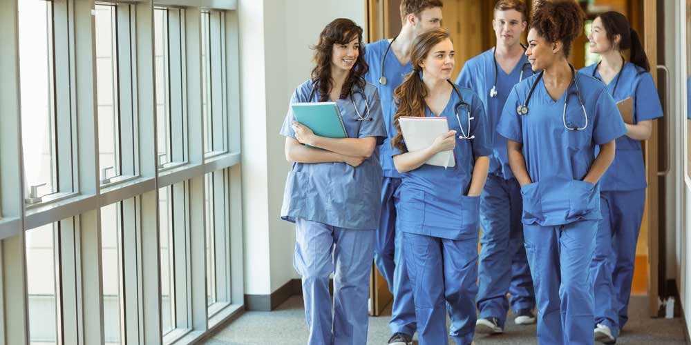 Healthcare students walk down a hospital hall.