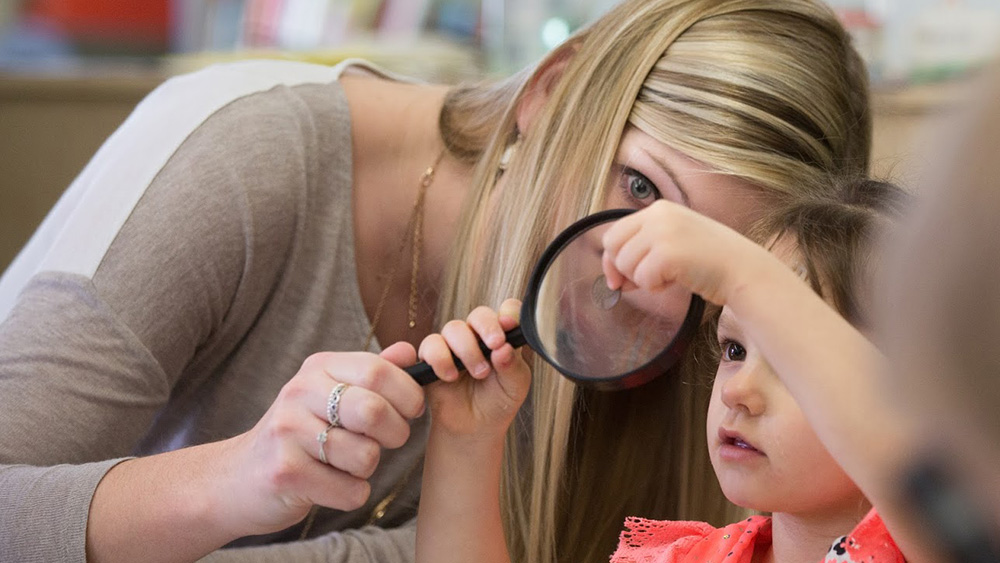 An instructor helps a young child hold a magnifying glass.
