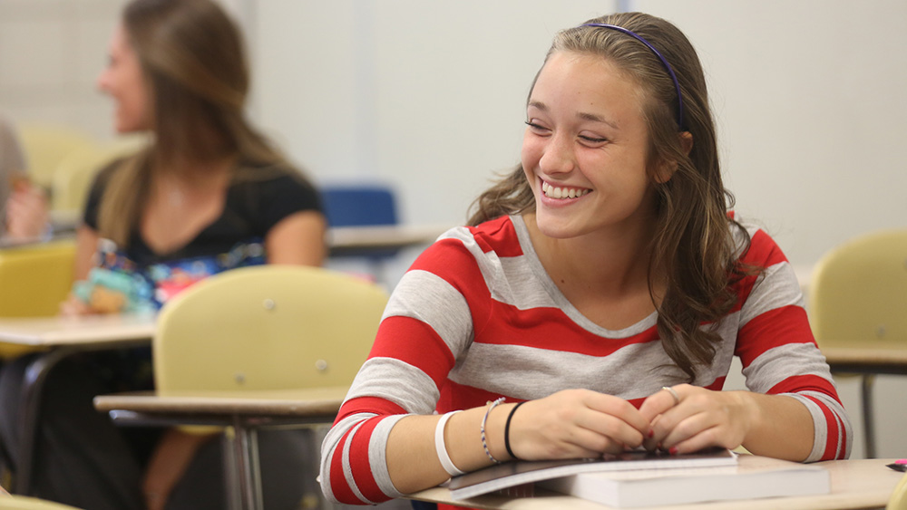A communications studies student sits in the classroom.