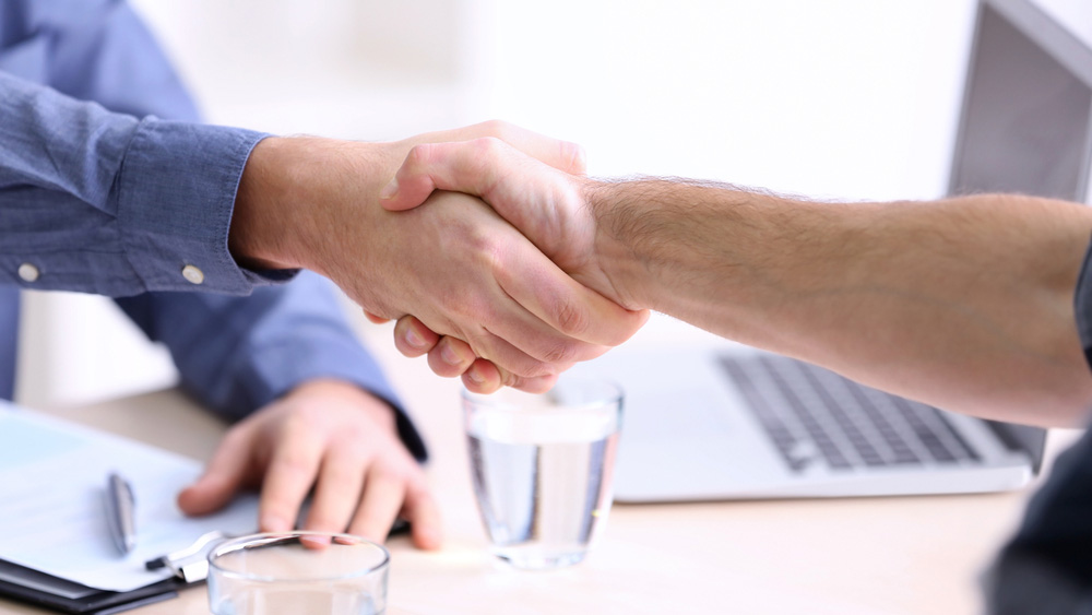 Handshake over table.