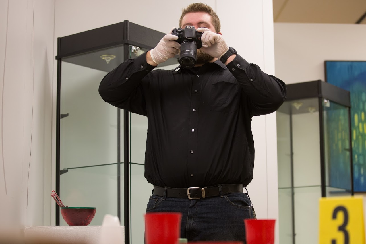 A man uses a camera to document evidence.
