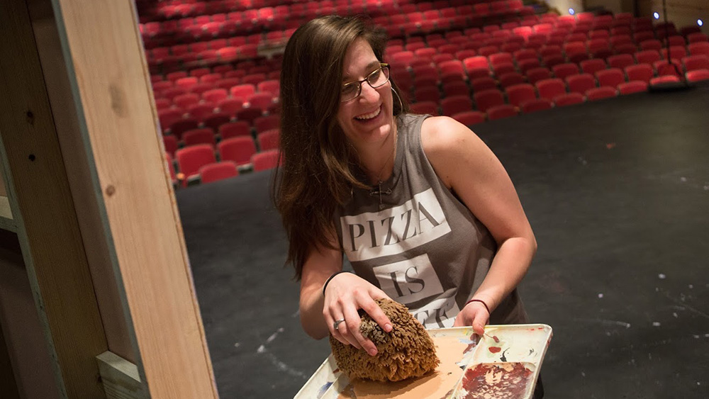 Cal U student helps paint a scene for the Theatre Department.