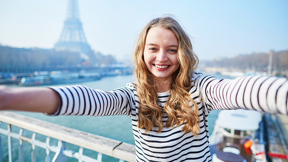 A student posing in Paris for a photo.