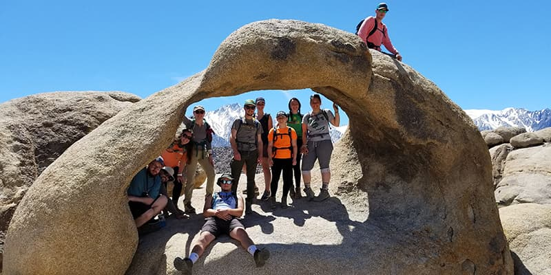 Students pose on geology rock formation.