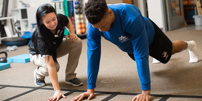 An athletic training students works with an athlete.