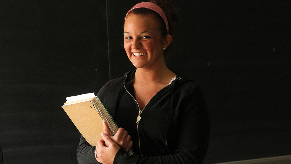 A smiling student poses with a book.