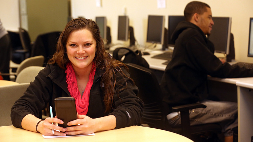 A smiling Cal U student in a classroom with a calculator.