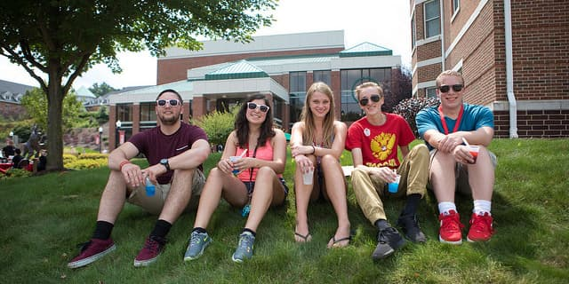 Cal U Students sit on a hill.