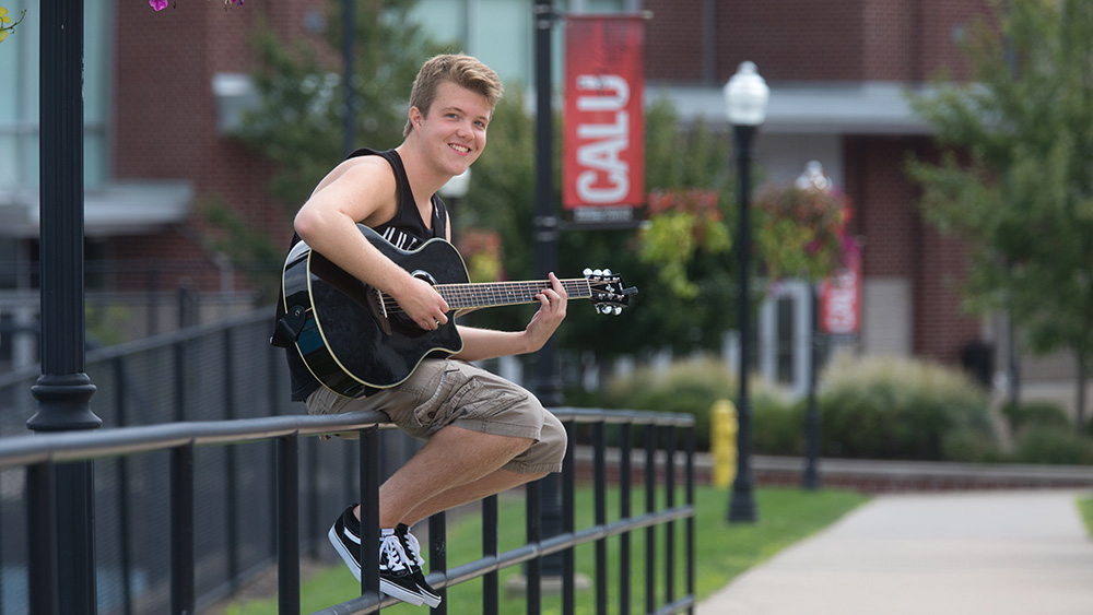A student plays the guitar on campus.