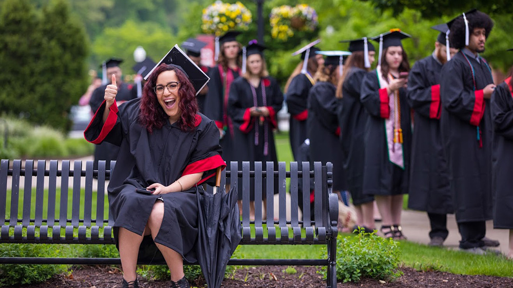 A Cal U musical theater graduate sits on bench with cap and gown.