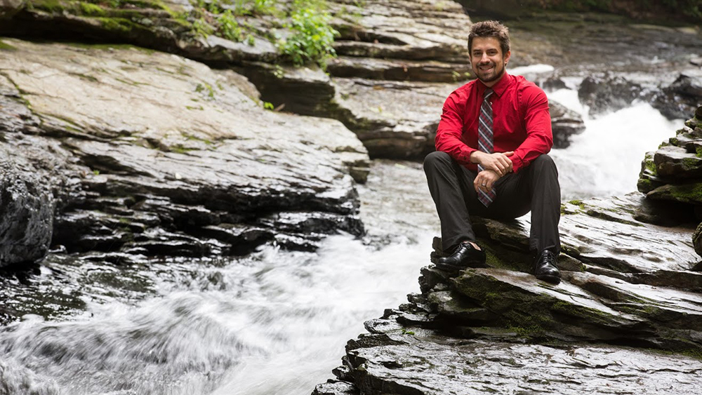 A Cal U student sits on rocks and Laurel Mountain park.