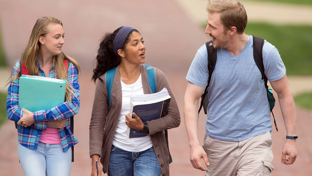 Students talk as they walk through campus.