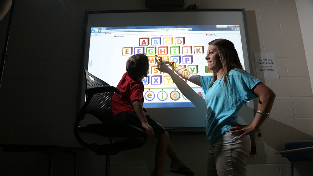 A young student is being taught the alphabet.