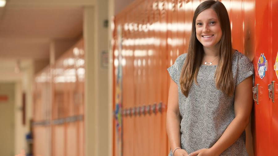 A teacher stands against lockers.