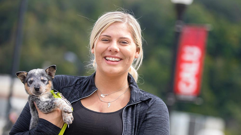 A Cal U students holds a dog on campus.