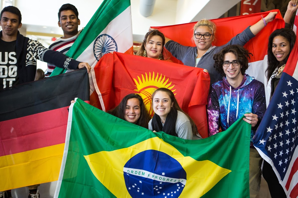 A group of students each hold a flag from another country.