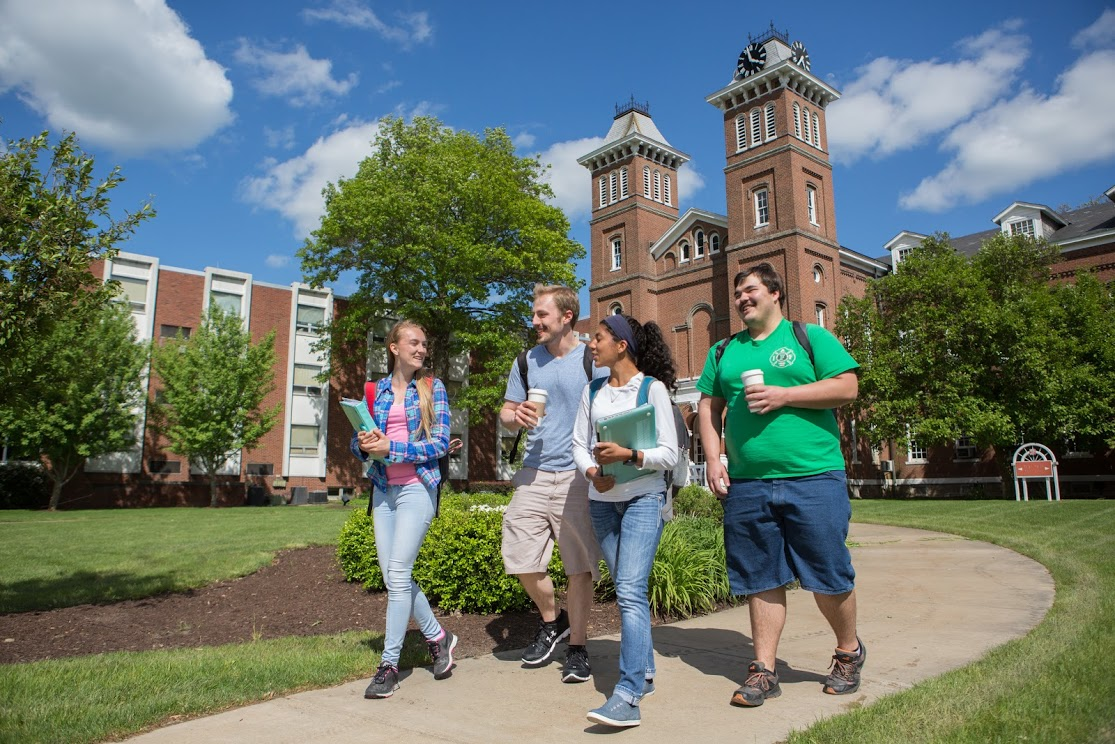Four students, holding books, walk across Cal U's beautiful campus on a bright, sunny day.