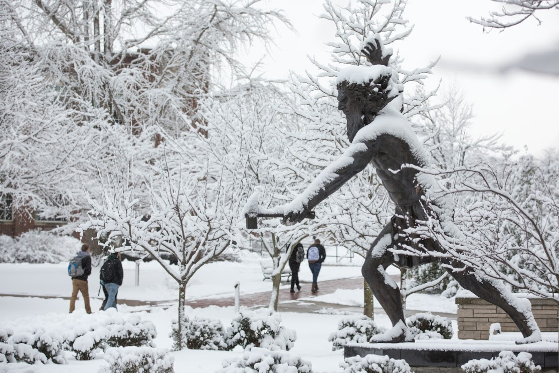A statue of Cal U's mascot, the Vulcan, stands snow-covered as students walk past to get to class.