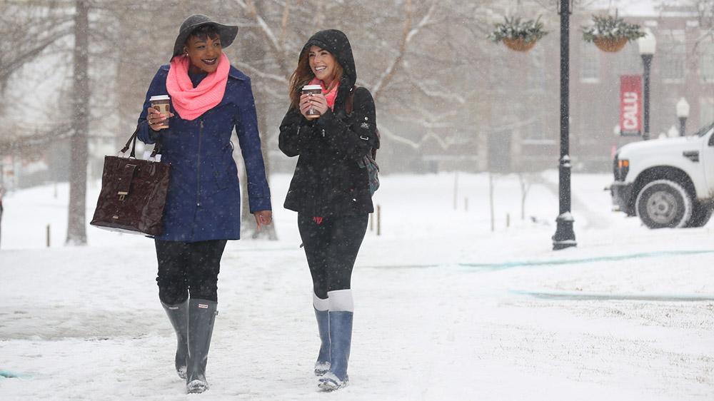 Two Cal U students walk outside on a winter day.