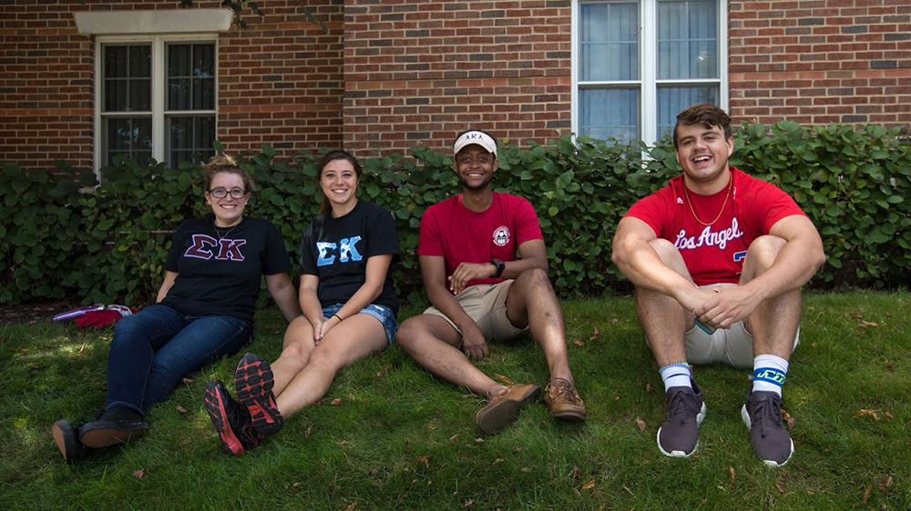 Students sit on lawn ourtside of residence halls.