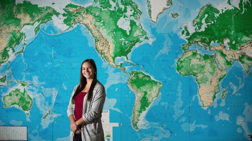 A international student poses in front of a map.