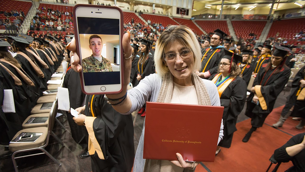 An active military student receives diploma via video conference.