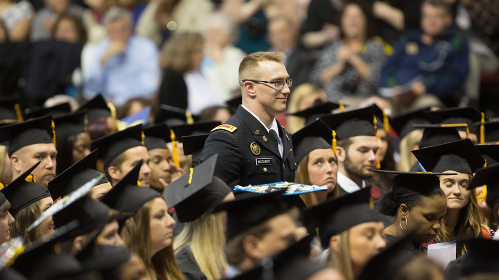 A military graduate stands during commencement.