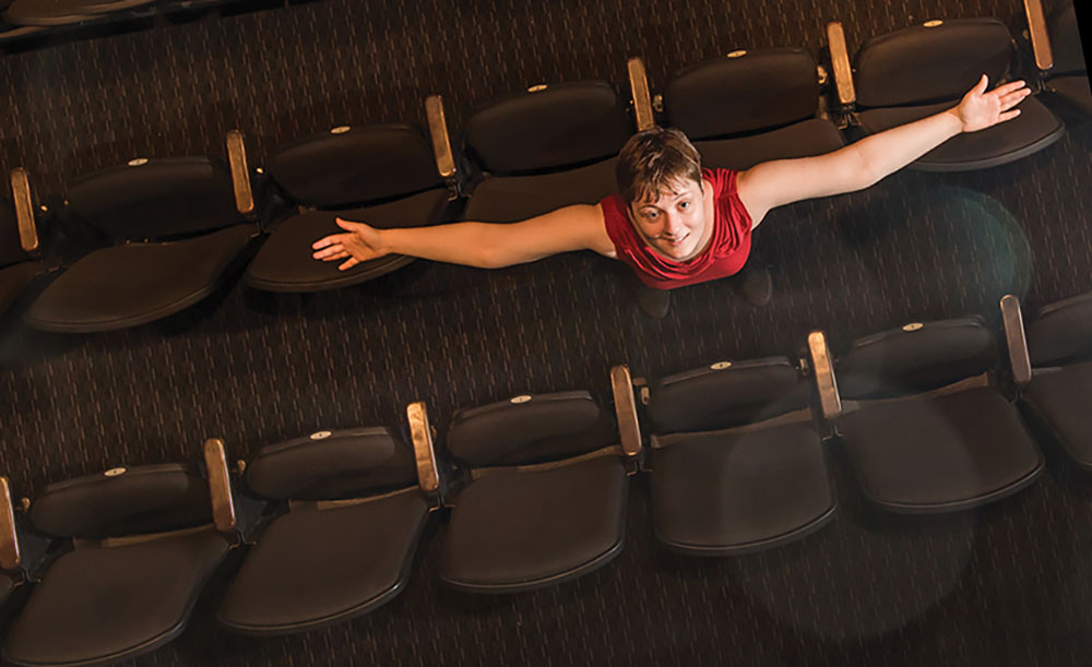 Alyssa Freeman looks upward with her arms stretched outwards in the aisle of theatre seating.