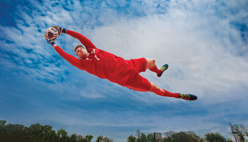 Lucas Exner catches a soccer ball by leaping into the air.
