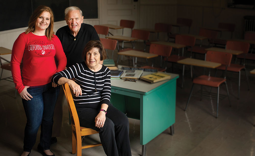 Rachel Wilkinson sits with family in a classroom posing for a portrait.