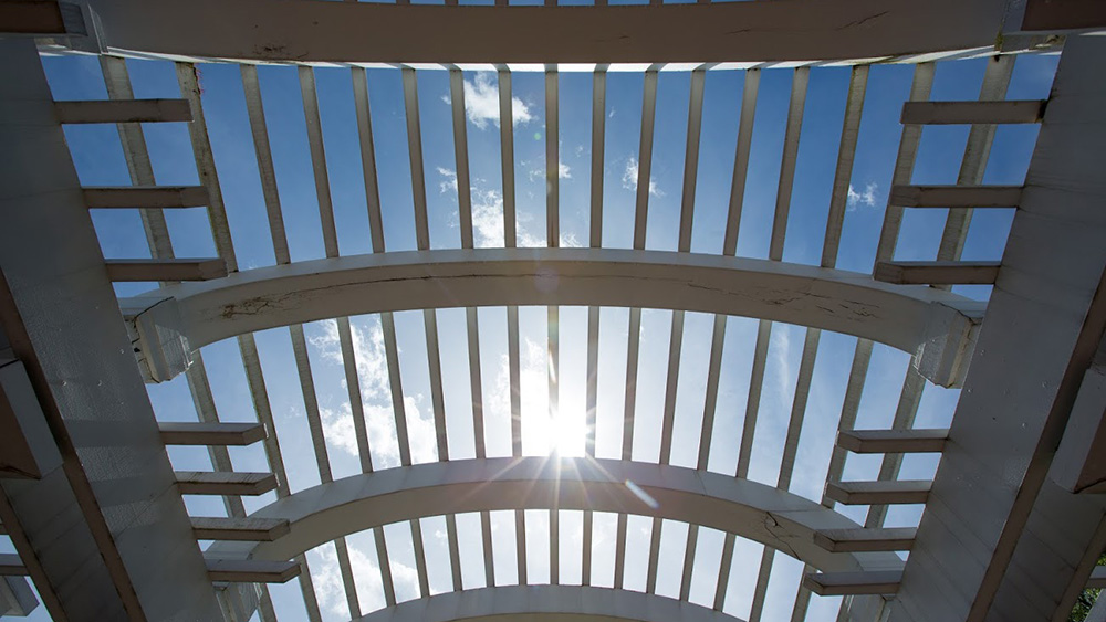 A pergola in the sun on campus gives students places to feel at home.