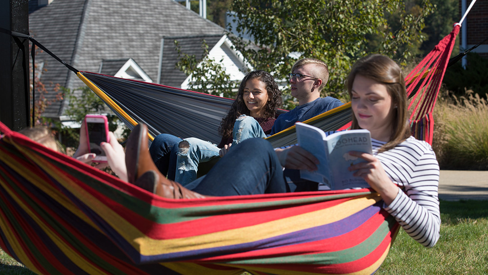 Students sit in a hammock.